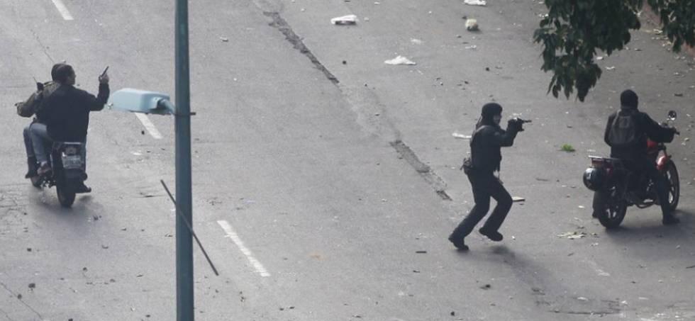 Paramilitares apontam armas para os manifestantes.