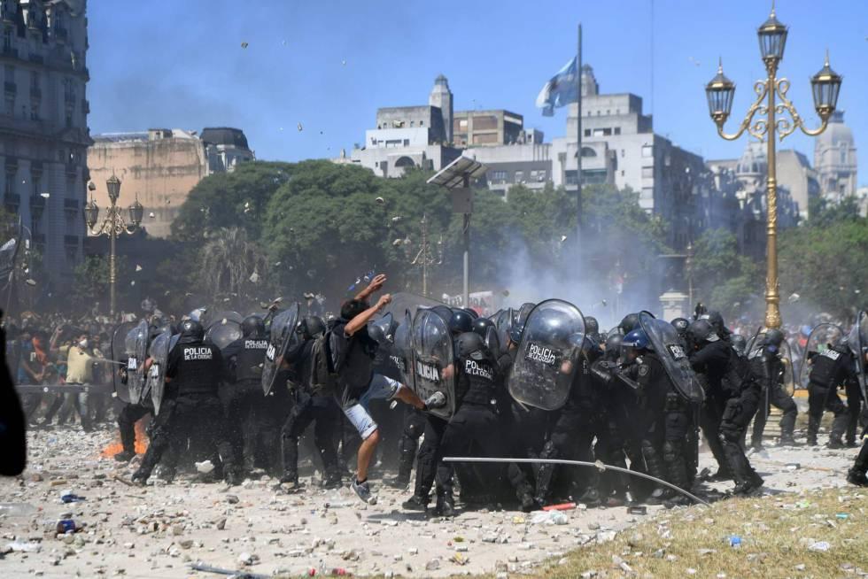 Manifestantes cercam grupo de policiais durante os distúrbios em frente ao Congresso argentino.