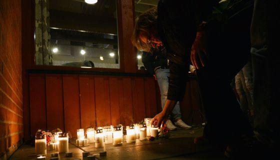 Mulher acende vela em memória às vítimas.