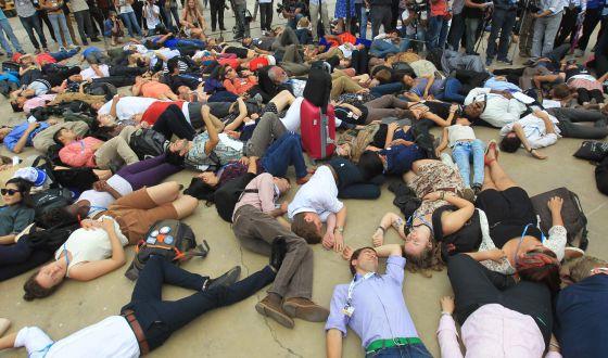 Centenas simulam estarem mortos diante do local onde ocorre conferência.