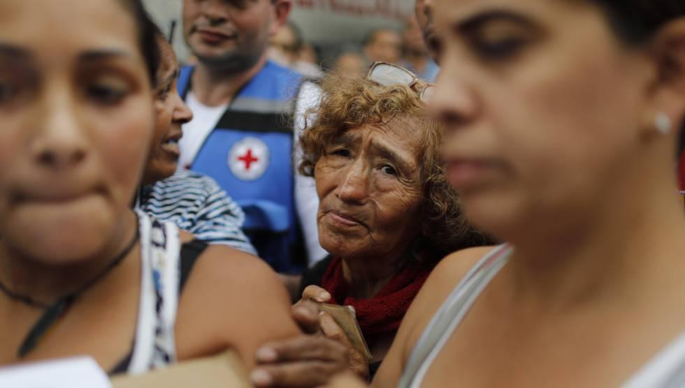 Venezuelanos esperam para receber água filtrada e medicamentos distribuídos pela Cruz Vermelha em Caracas.