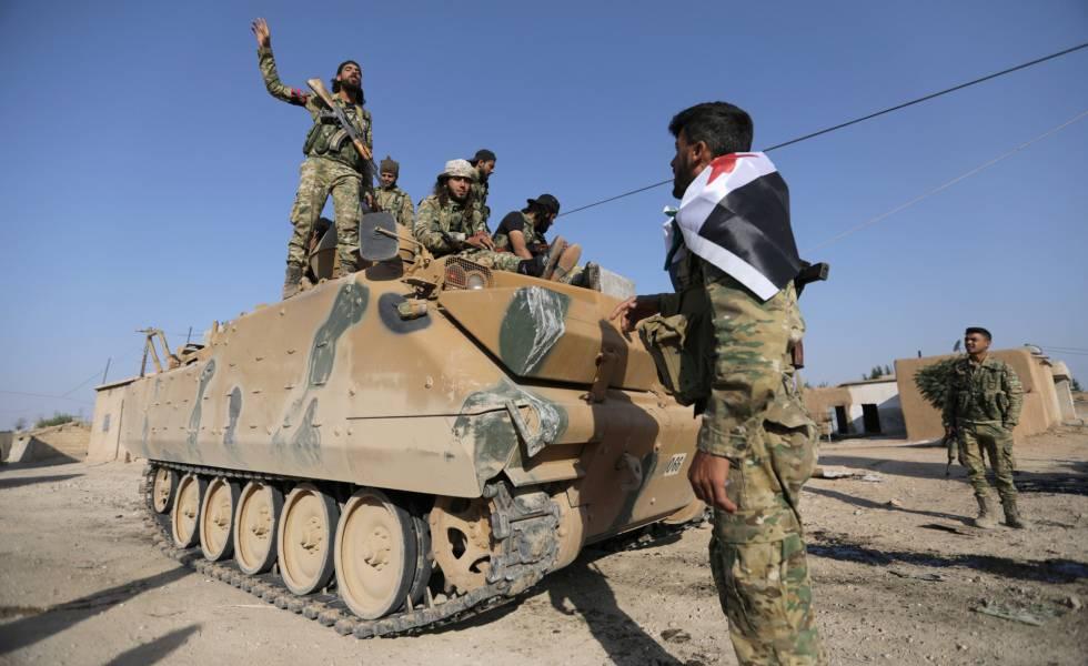 Soldados rebeldes sírios apoiados pela Turquia, num veículo militar na aldeia de Yabisa, perto da fronteira entre os dois países.