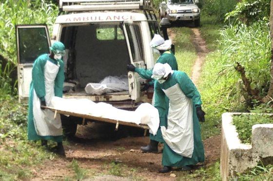 Sanitaristas transportam o corpo de uma vítima do ebola, em junho, em Kenema, Serra Leoa.