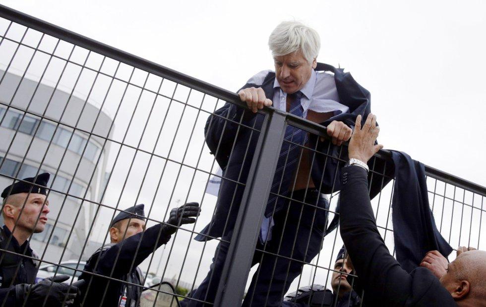 O diretor de recursos humanos de Air France pula uma cerca escoltado pela polícia para fugir da sede da companhia. Durante uma reunião do comitê central da companhia aérea, a sede da empresa foi invadida por várias centenas de empregados em protesto pelo plano de ajuste que contemplava a demissão de 2.900 pessoas.
