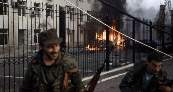 Separatistas pró-russos se afastam de carro em chamas, em Donestk.