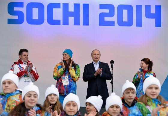 Vladimir Putin e a saltadora Elena Isinbayeva (de gorro azul), em Sochi.