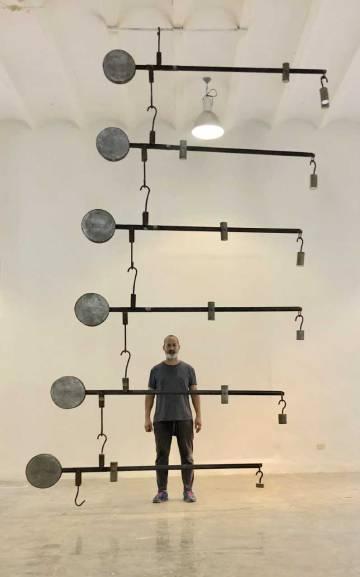 O artista Marco Castillo com sua obra 'Gabriel', na 13ª Bienal de Havana.
