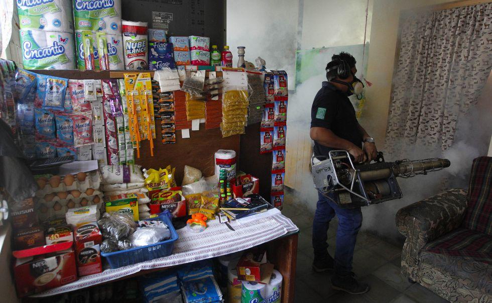 Funcionário do Ministério da Saúde de El Salvador fumega uma casa.