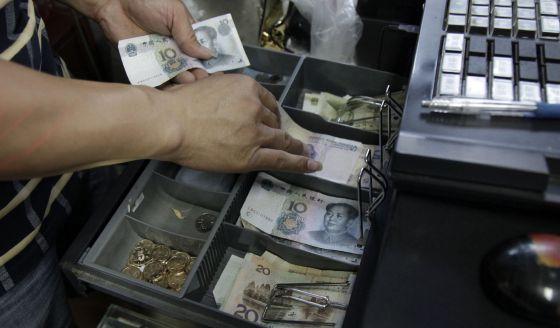 Funcionário do Banco da China contabiliza notas e moedas.