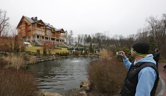 Um homem tira fotos da mansão de Víctor Yanukóvich.