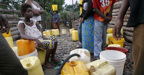 Várias pessoas coletam água em Copperbelt, no norte da Zâmbia.