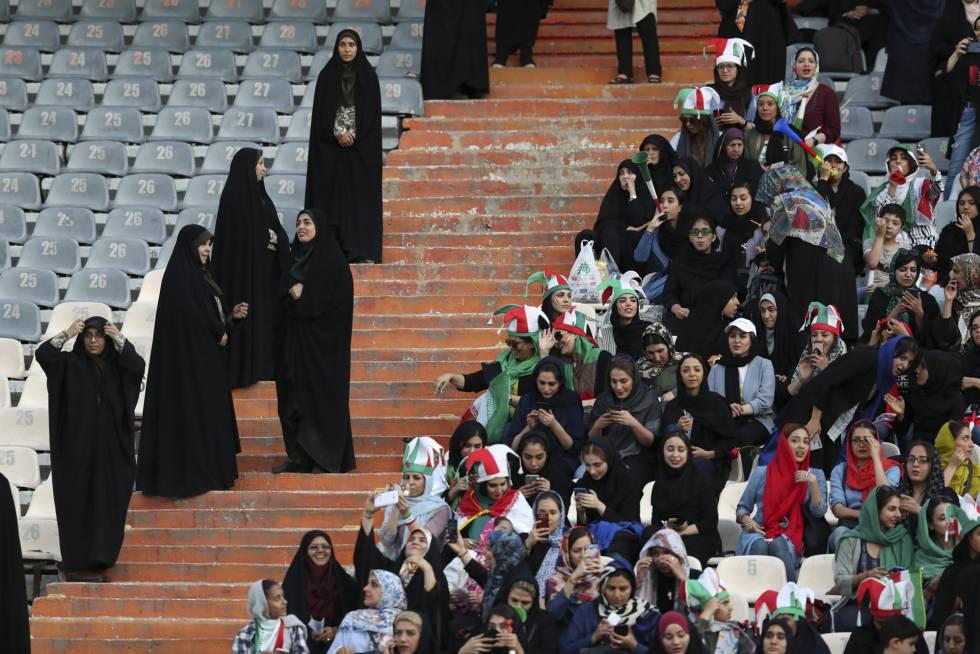Torcedoras iranianas na grade do estádio Azadi, vigiadas por policiais.
