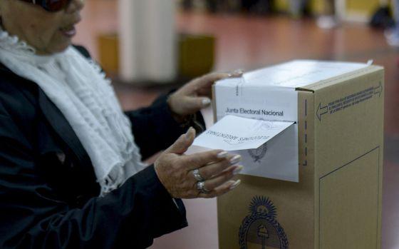 Uma mulher deposita seu voto em Buenos Aires.