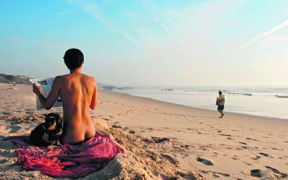 Uma jovem com seu cão na praia portuguesa do Malhão.