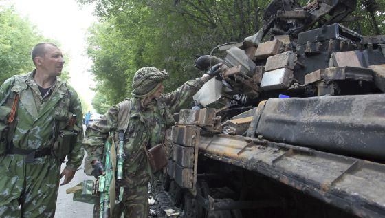 Militantes pró-russos observam os restos carbonizados de um tanque ucraniano perto de Donetsk.