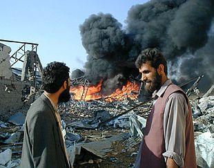 Un afgano conversa con un empleado de la Cruz Roja frente a unos escombros en llamas, lo único que queda de los edificios de la organización humanitaria en Kabul.