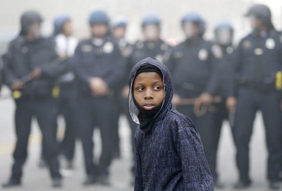 Um garoto diante da polícia, durante os protestos de segunda-feira em Baltimore.