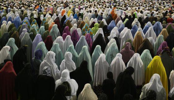 Muçulmanas rezam diante da Grande Mesquita de Meca, em 2009