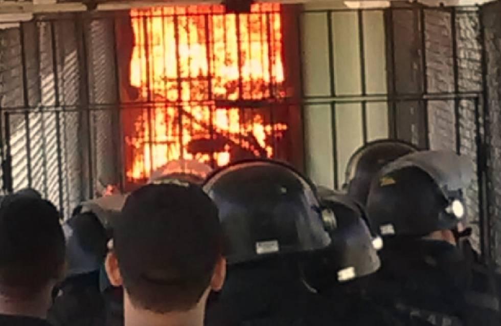 Policiais observam corredor de presídio CPPL IV em chamas durante rebelião.