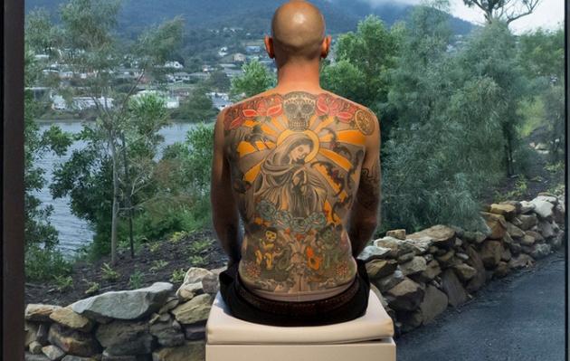Tim Steiner posando como obra de Wim Delvoye em um museu da Tasmânia.