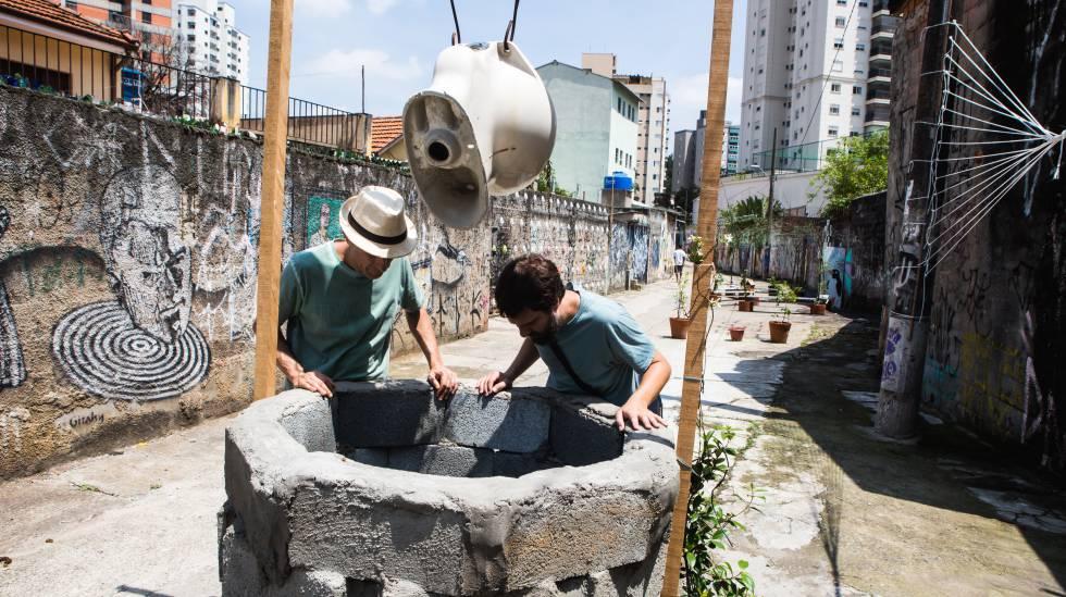 Adriano Sampaio, do Existe Água em SP, e o artista Flavio Barollo, do grupo (se)cura humana, observam o córrego Água Preta, em São Paulo