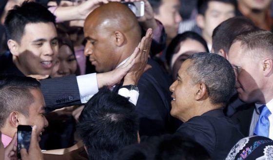 Barack Obama bate sua mão com a de um jovem durante encontro em uma Universidade em Kuala Lumpur.