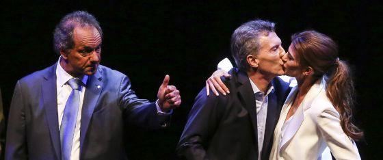 Macri recebe o beijo de sua esposa enquanto Scioli cumprimenta o público após o debate eleitoral de 18 de novembro.