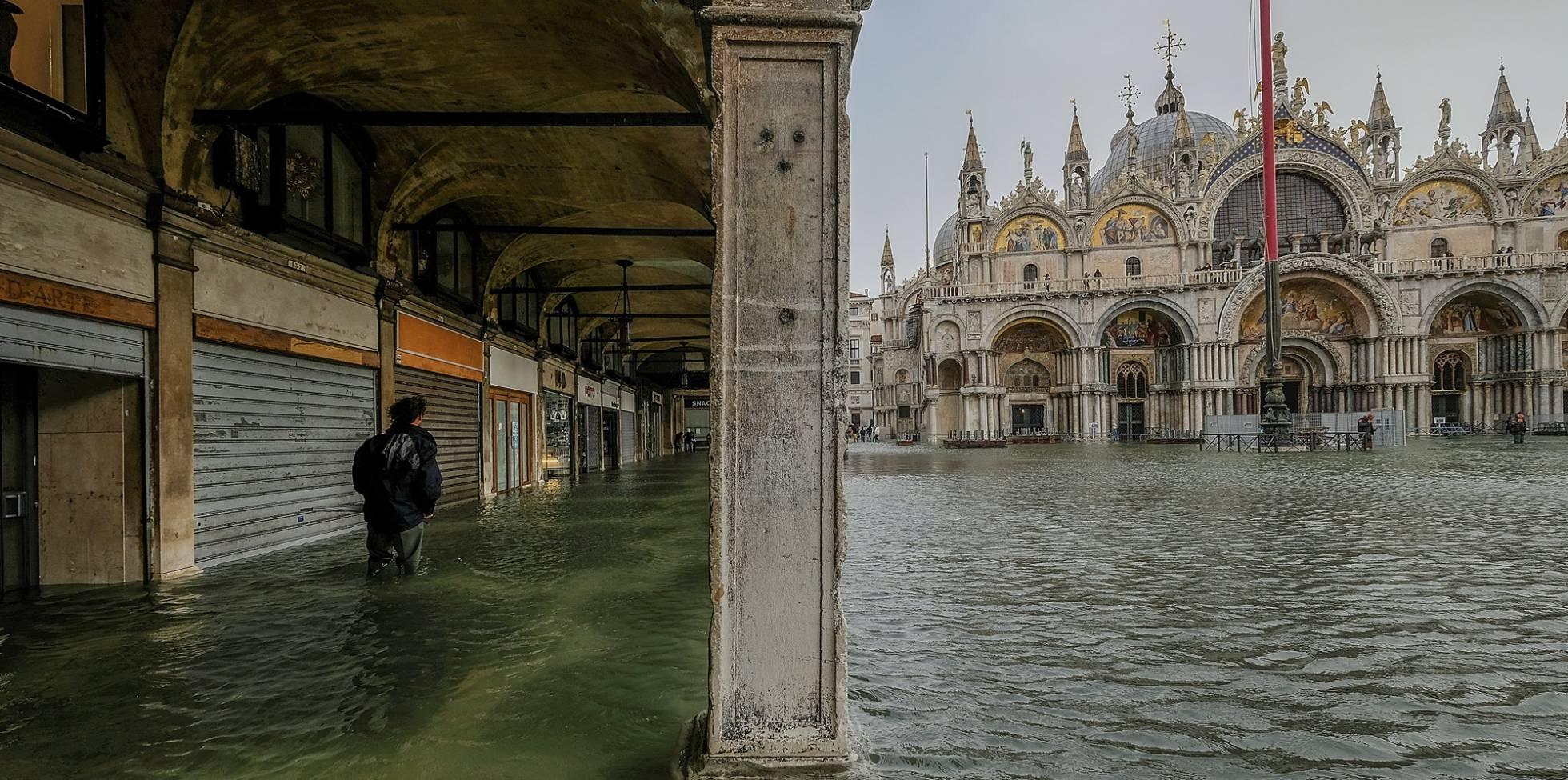 Um turista caminha pelas ruas alagadas em Veneza.