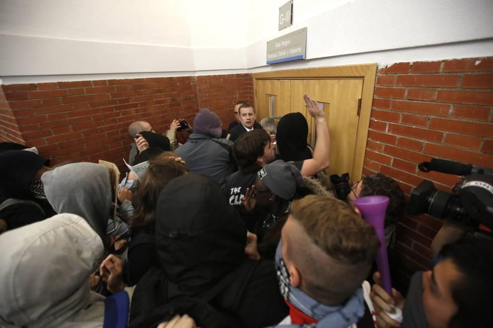 Vários encapuzados esmurram a porta onde deveria acontecer uma cerimônia na Universidade Autônoma.
