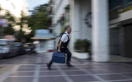 Segurança leva dinheiro a uma sucursal bancária em Atenas.