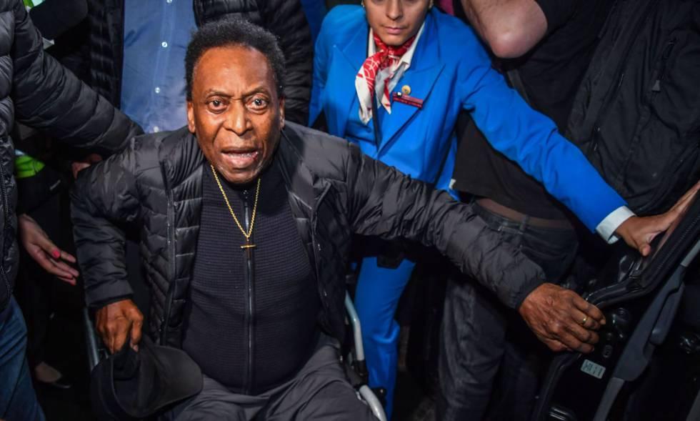 Pelé é transportado em cadeira de rodas no aeroporto de Guarulhos.