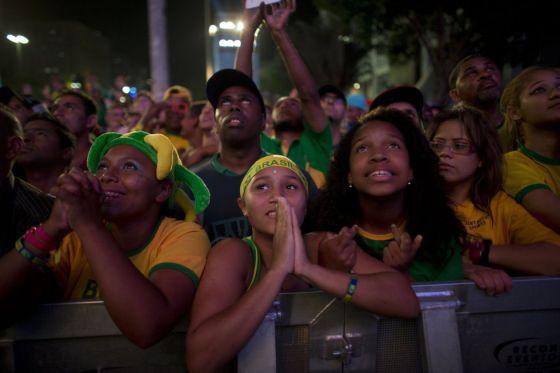 Torcedores brasileiros assistem à seleção em um telão.