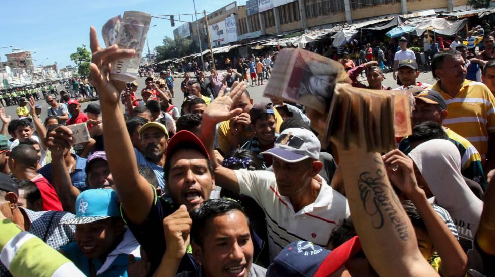 Venezuelanos mostram notas de 100 bolívares