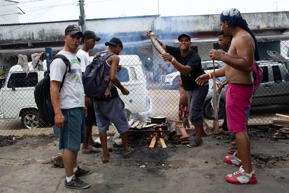 Grupo de venezuelanos assa peixe em churrasqueira improvisada, perto da estação de ônibus de Manaus