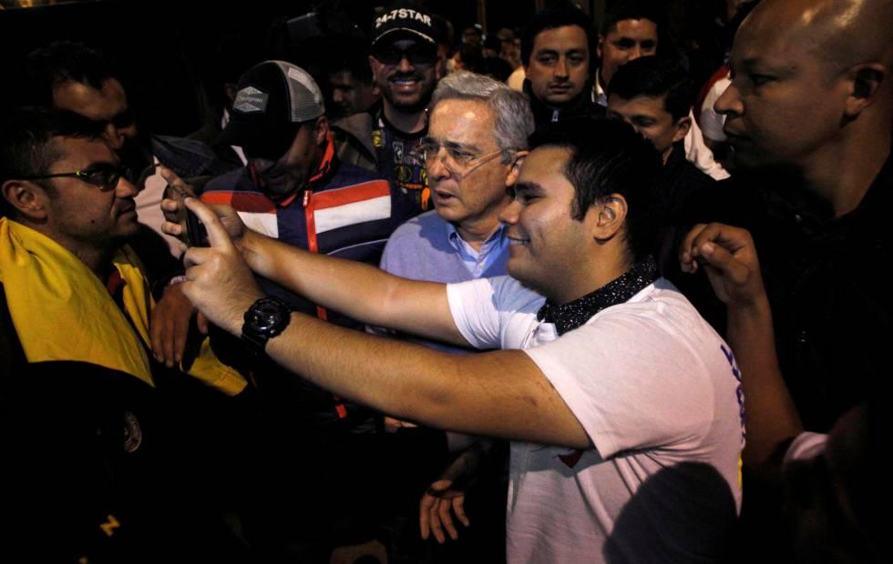 O ex-presidente colombiano Álvaro Uribe posa para um 'selfie' com um partidário do 'não' ao acordo de paz, no domingo.