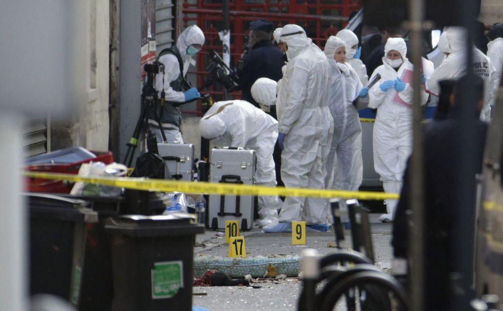 Forenses trabalham buscando provas depois da operação policial em Saint-Denis, ao norte de Paris.