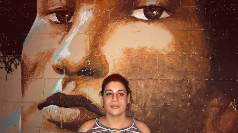 Professora Luiza Coppieters em frente a grafite de Marielle Franco