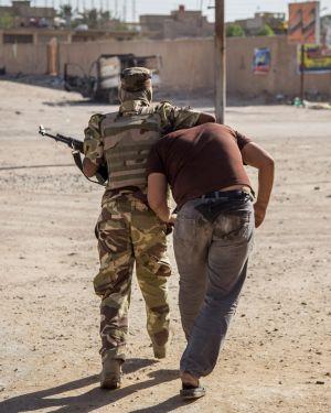 Um soldado detém um suspeito em Kerbala.