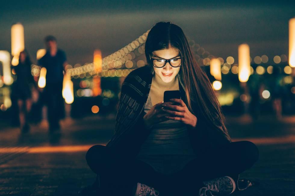 Uma jovem consulta seu celular.