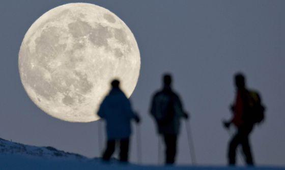 Três praticantes de esqui de montanha contemplam a lua cheia em Weissfluhjoch, em Arosa (Suíça), um dia antes do solstício de inverno.