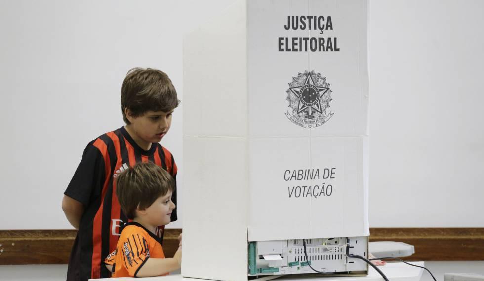 Crianças olham para urna eletrônica durante sessão em colégio eleitoral de São Paulo.