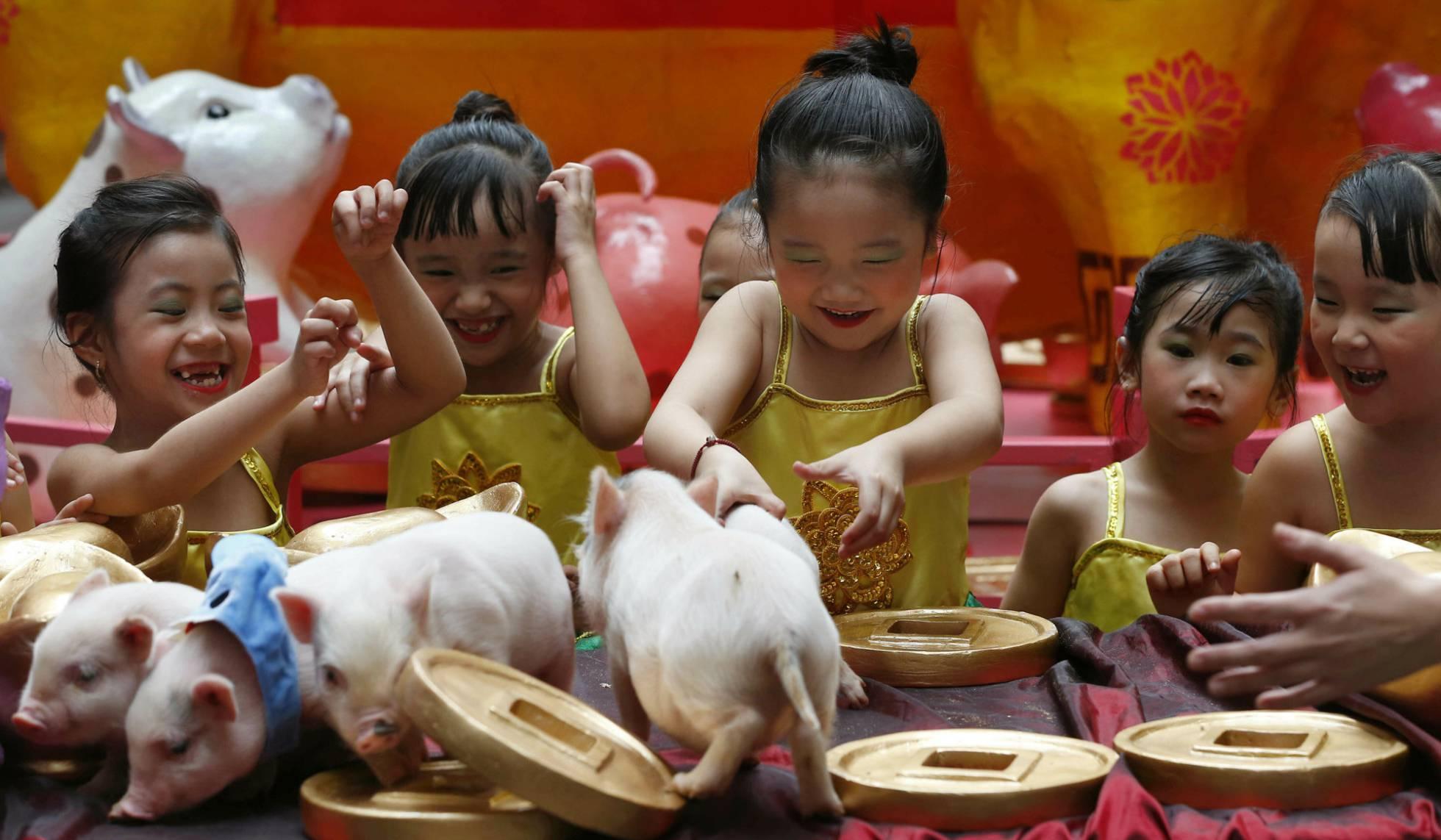 Crianças brincam com porquinhos em Manila, nas Filipinas.