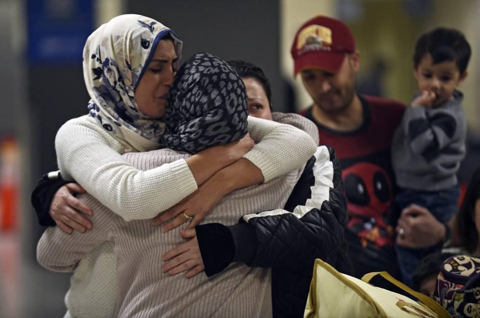 Uma família iraquiana recebe uma mulher que não podia viajar por conta do veto, no domingo no aeroporto de Dulles, Virgínia.