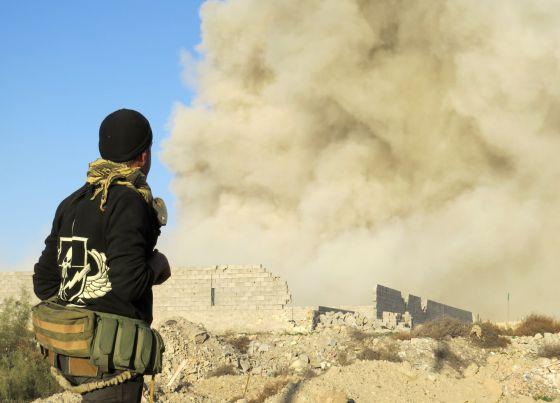 Um combatente pró-governo observa uma coluna de fumaça em um bairro de Ramadi hoje durante a ofensiva do Exército.