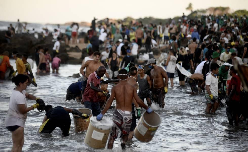 Na Pedra de Xaréu, Cabo de Santo Agostinho, Pernambuco, uma multidão de voluntários se organiza como pode para retirar o óleo da praia