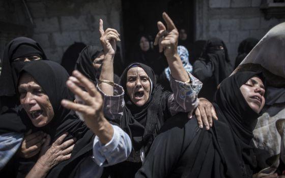 Mulheres palestinas no enterro de uma família morta em um bombardeio.