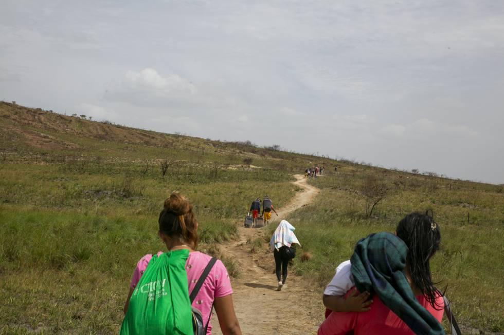 Venezuelanos atravessam a pé a fronteira entre Venezuela e Brasil.