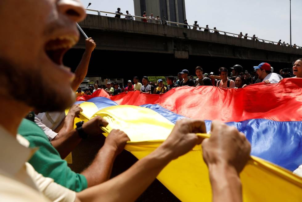 Manifestantes contrários a Maduro erguem bandeira da Venezuela.