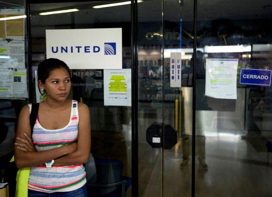 Uma mulher espera diante de um escritório da United em Caracas.