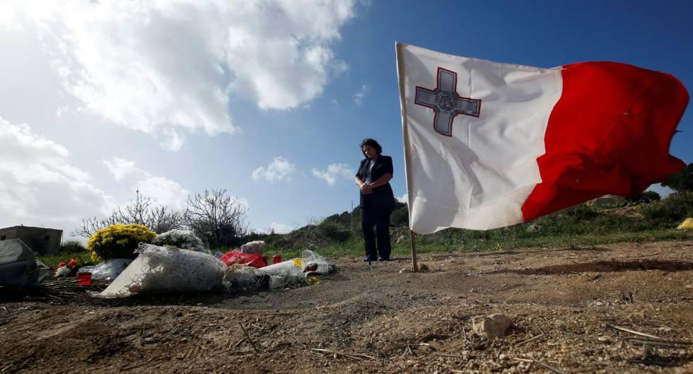 Mulher visita o local do assassinato da repórter Daphne Caruana Galizia.